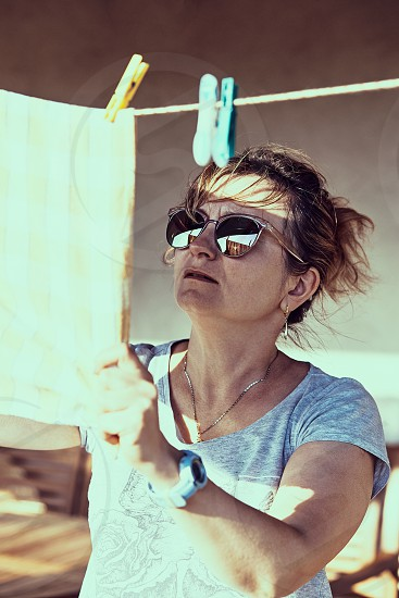 Adult woman hanging a laundered cloth on clothesline. Real people real authentic situations photo