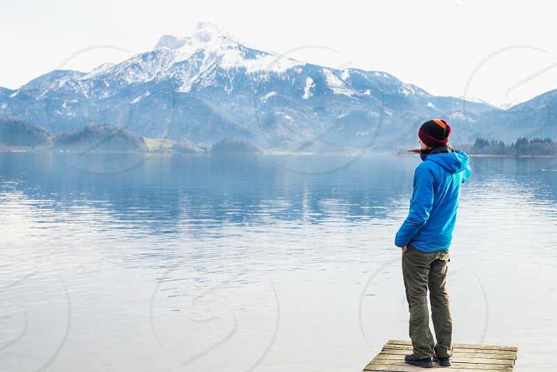 The man looking at the mirror lake and the mountains at the background with clear blue sky in cold weather photo