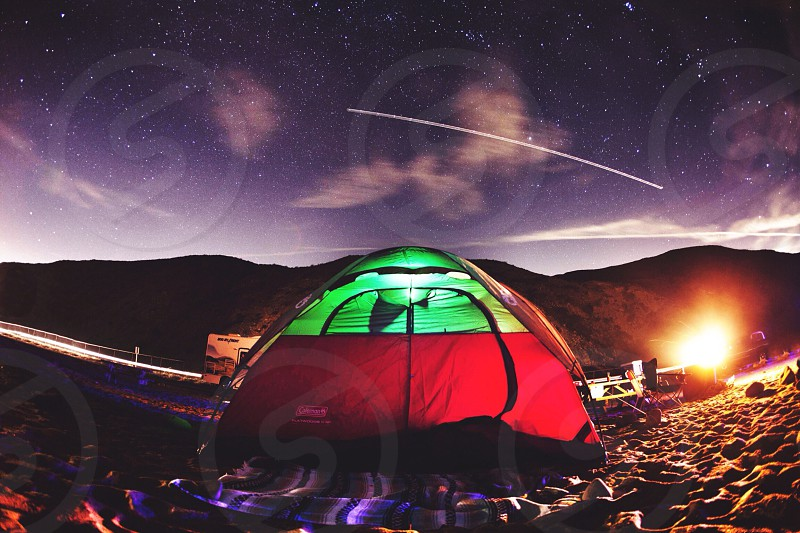 tent on sand with mountain and shooting star on sky photo