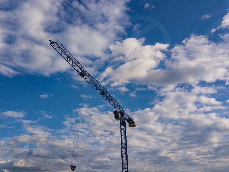 A raised construction crane against the blue sky and white clouds on a summer day at the building site raises the cargo. photo