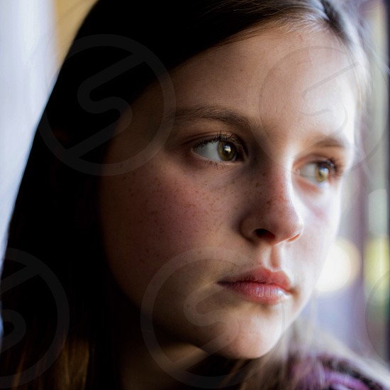Young girl gazing out a window with a serious expression  photo