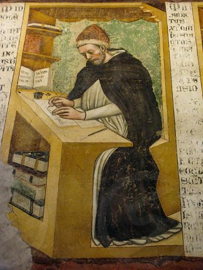 One of the monks pictured in a fresco in the monastery chapter house of San Nicolo church in Treviso Italy is this one seated at a desk copying a manuscript in the scriptorium. photo