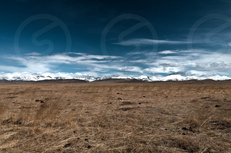 The vast expanse of sky and land meet at the jagged mountains on the edge of the grasslands of eastern Tibet. Tibet grassland travel adventure landscape sky horizon photo