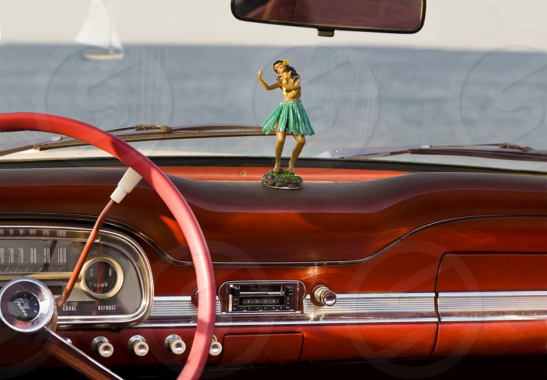 Hawaiian woman in green skirt figurine in front of car red steering wheel photo