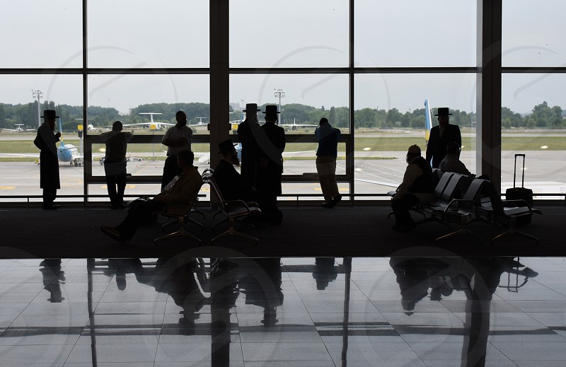 people near clear glass window with other people sitting on metal chairs inside airport photo