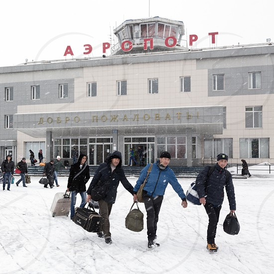 PETROPAVLOVSK-KAMCHATSKY KAMCHATKA RUSSIA - MARCH 19 2015: Winter view of the airport terminal Petropavlovsk-Kamchatsky (Elizovo airport) and the station square with the people with baggage. photo