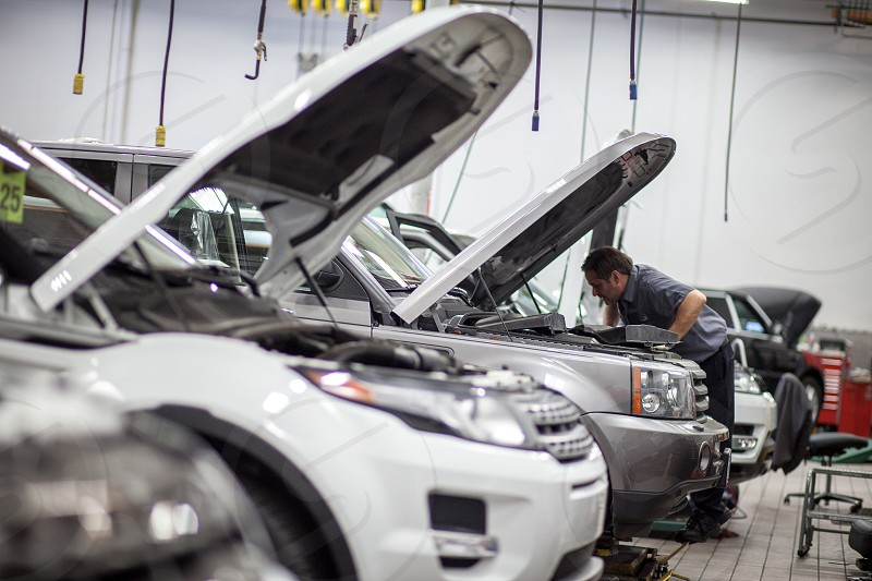 A mechanic works on the engine of an SUV in a large garage with several vehicles. photo