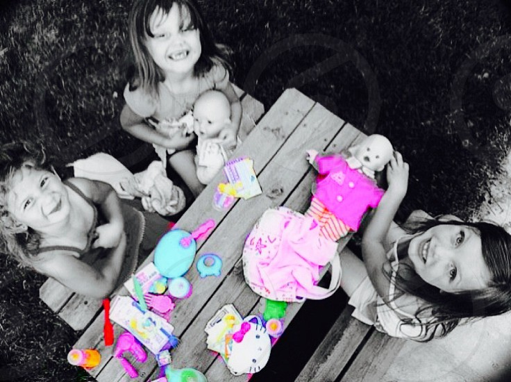 selective color photography of three girls playing with dolls on table photo