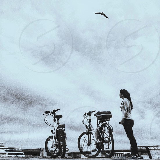 woman standing in front of bicycle photography photo