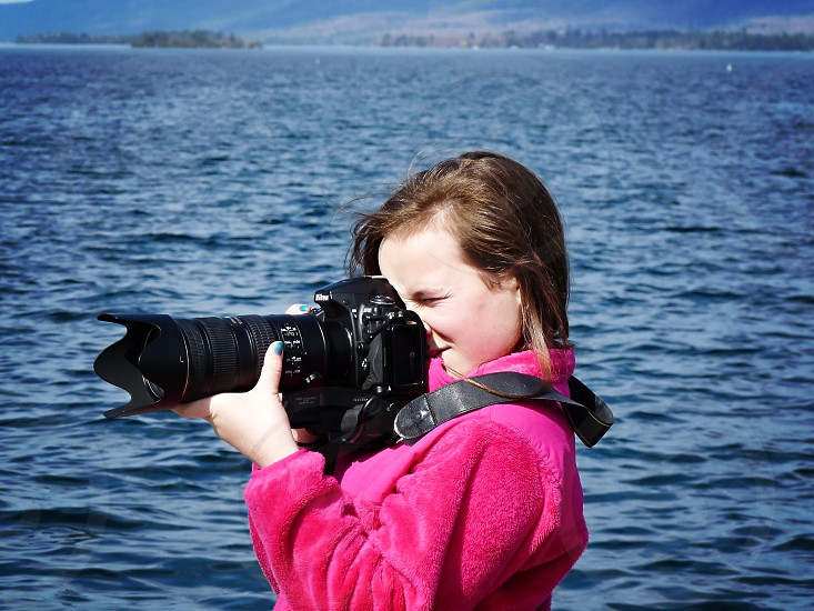 Young girl following in her fathers footsteps as a photographer. The girl hold a DSLR. photo