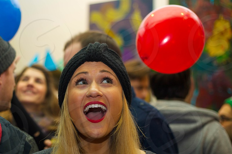 woman wearing black knit cap smiling with other people in background during daytime photo