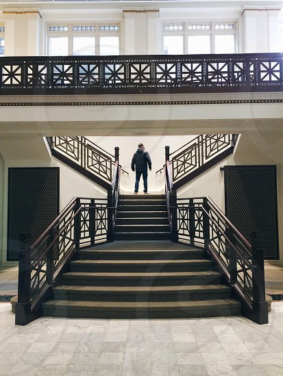 man in black jacket and blue denim jeans on the stairs photo