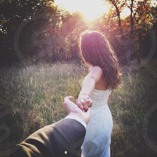 woman in white beaded strapless gown leading a man into the woods photo