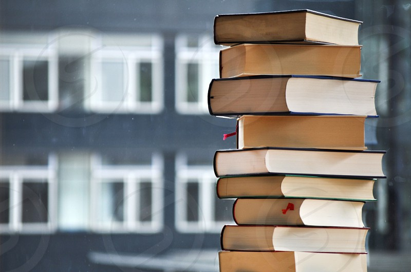stacked books in front of black building with white trim photo