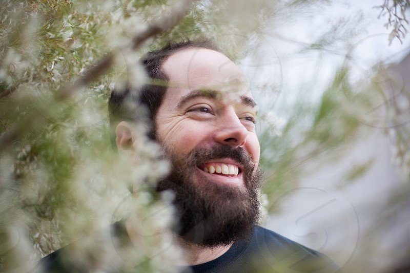 A bearded man looks out into the distance smiling amongst a floral tree bokeh background photo