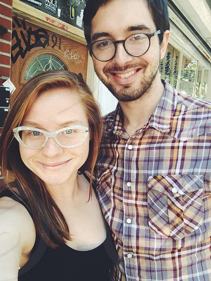 man and woman in eye glasses selfie outside restaurant photo