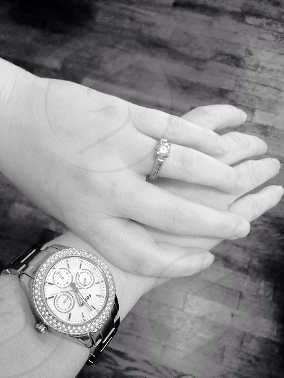 Black and white image of clasped hands exposing jewelry. photo