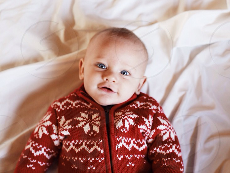 baby in red and white floral sweater smiling photo