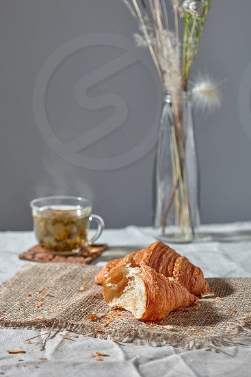Delicious morning breakfast setting with french homemade pastry cup of green aromatic fresh tea and flower's vase on a grey textile background. Place for text. photo