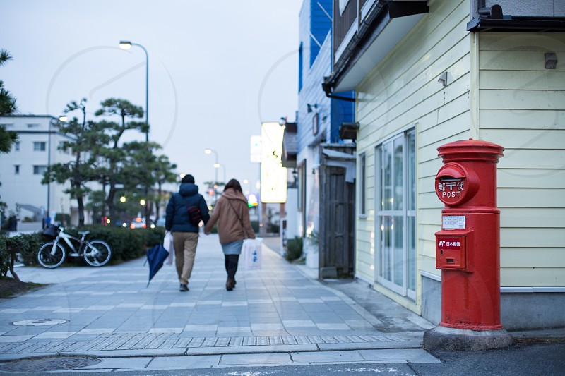 Red post boxes and two people photo