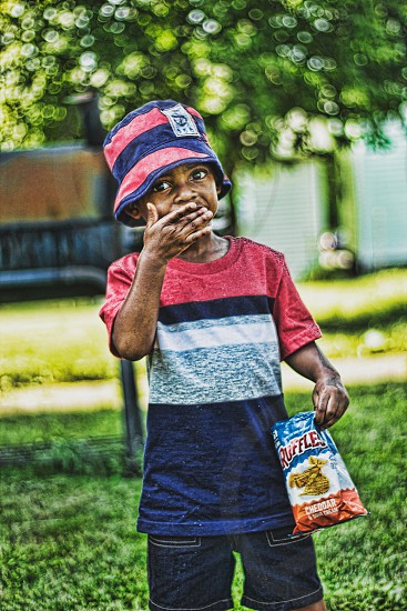 edited photo of boy holding Ruffles pack on his left hand while putting his right hand on his mouth photo