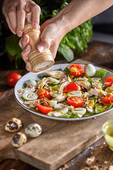 Delicious natural salad with fresly picked green vegetables chicken meat and womans hands salt it on a wooden board. Concept of healthy diet food. photo