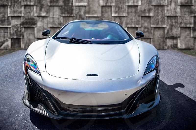 Exotic Luxury Collector Sports Car.  Silver grey McLaren wall texture nose face symmetry asphalt 650S British. photo