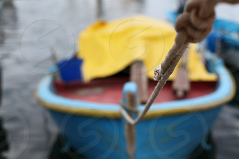 selected photo and close up photography of a blue and yellow canoe boat during day time photo