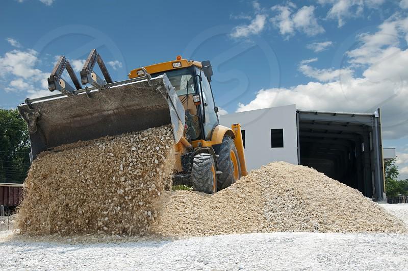 Yellow excavator unload gravel photo