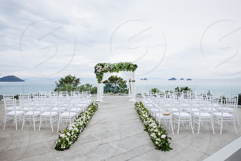 Beach Wedding venue outdoor with panoramic ocean view in the background. The white chairs for the guest the white and green flowers floral decoration for arch and the aisle. photo