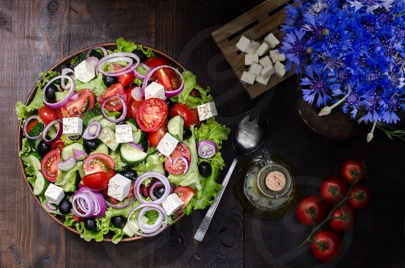Greek salad in brown bowl with ingredients on dark background photo