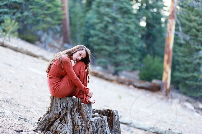 woman with long hair in red long sleeve dress in tuck position on grey tree stump on the slope during daytime photo