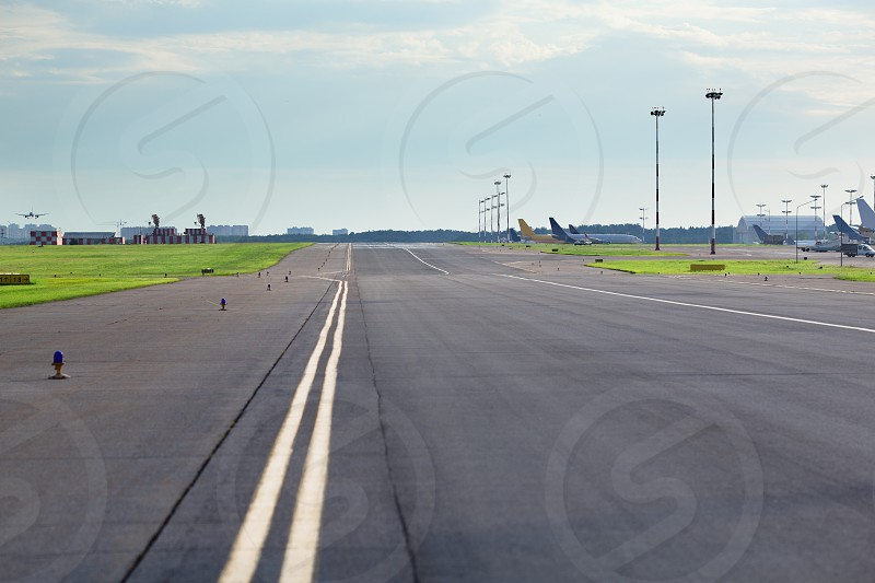 Empty airport asphalt runway with yellow marking airplanes in the background photo
