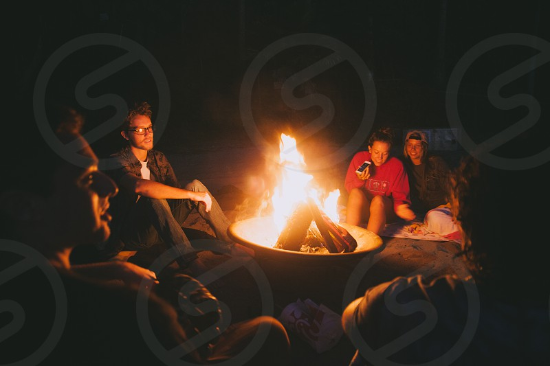 people sitting around camp fire during night time photo