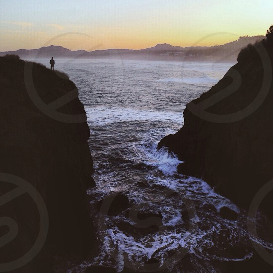 person standing on cliff near water photo