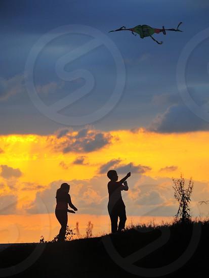 boy silhouette flying a kite photo