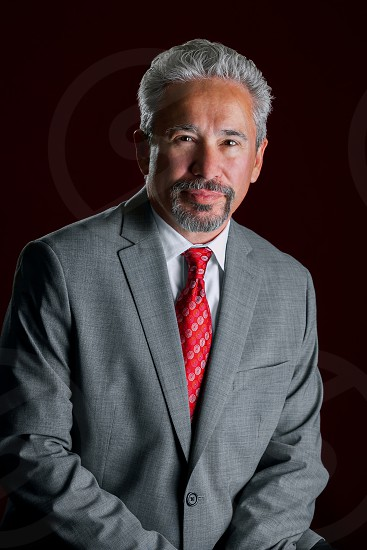 Studio portrait of an older handsome latino business man.  He is leaning in front of a dark red background. The light is dramatic. photo