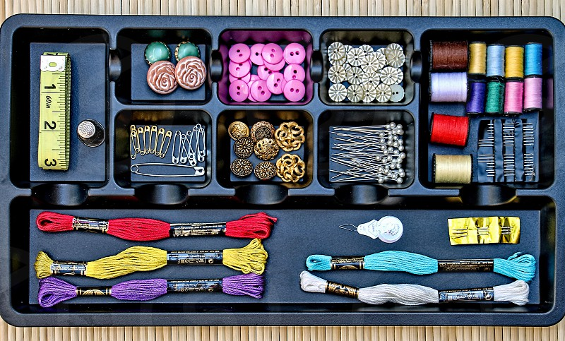 Aerial view of thread buttons pins and other sewing supplies organized in a tray photo