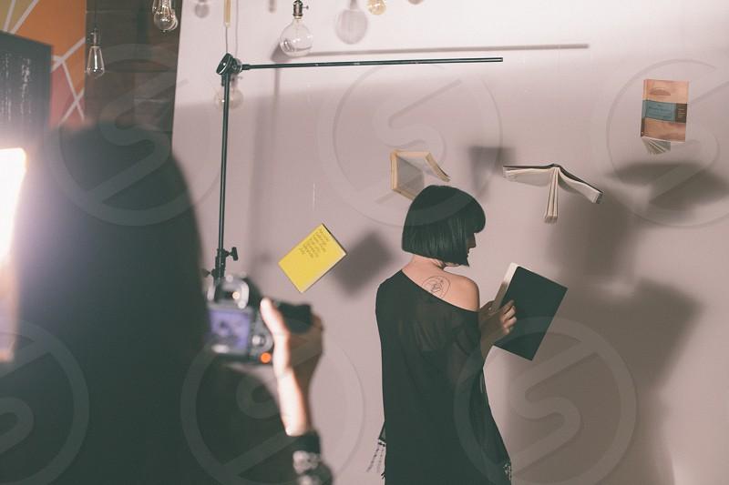 woman in black taking photo of brunette woman in black dress standing facing wall in studio photo