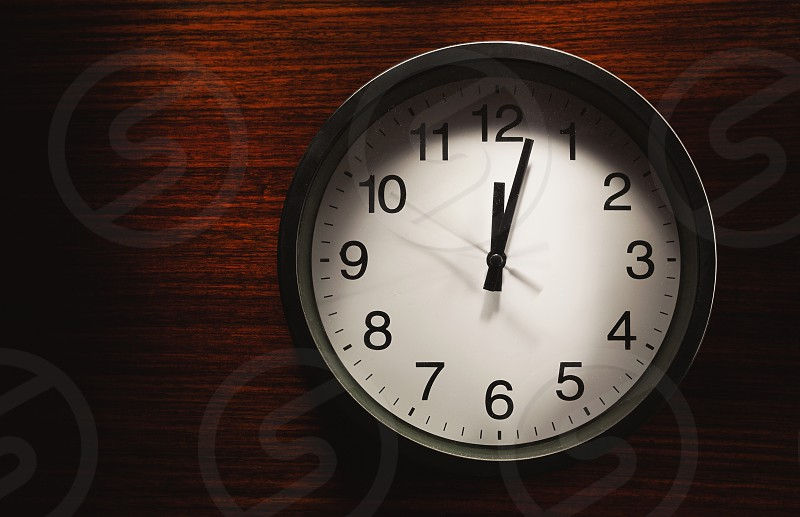 Simple composition black wall clock on wooden surface showing twelve o'clock. photo