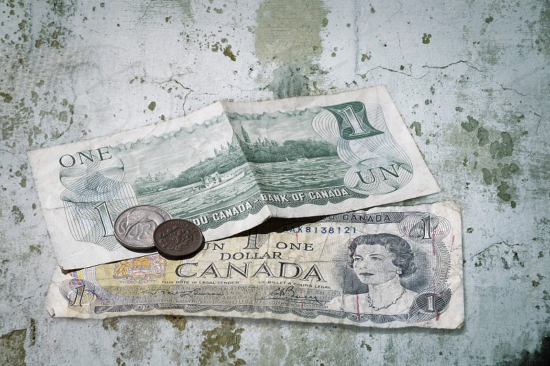 Canadian Dollars with a Luxembourg and Swordfish coin on concrete background photo
