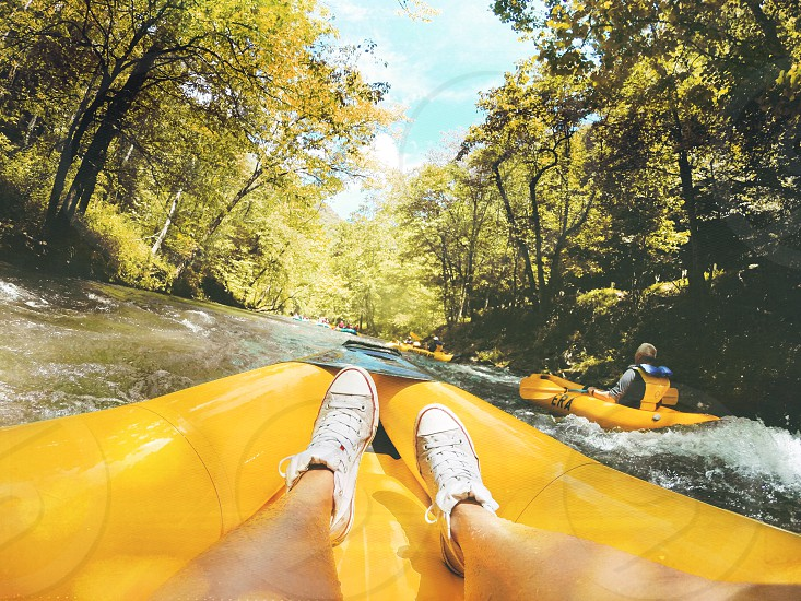 person on yellow inflatable raft on brown water surrounded by yellow leaf trees under white and blue sky during daytime photo