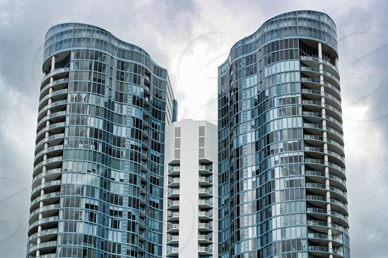 Two modern office towers reflect the clouds. photo