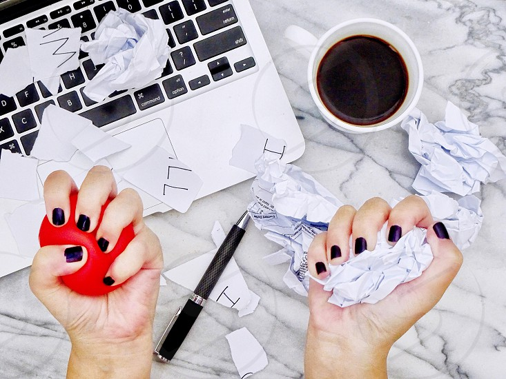 Stress anger stress relief burnt out frustration mental health emotional wellbeing sad working lifestyle working desk difficult hardship feelings technology coffee overhead shot working desk hands in frame divorce breakup tired strained overworked stress ball angry photo