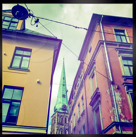 Outdoor day colour square filter Riga Latvia travel tourism tourist wanderlust Europe European Spring Summer Sky clouds blue Architecture Street traditional colourful lantern wires cables overhead colourful alley alleyway spire copper photo