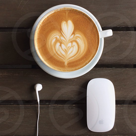 white apple computer mouse beside a white ceramic cup photo