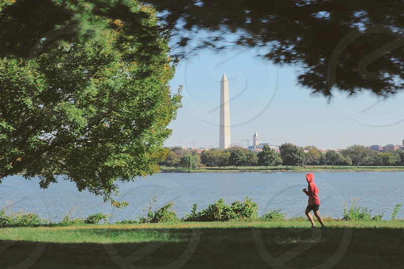 man running in grass near water with monument in distance photo