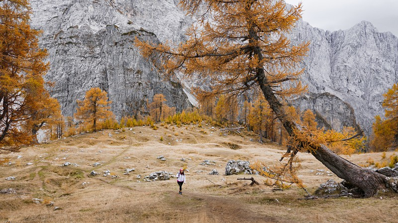 Young woman hiking in the mountains. Epic view. Yellow and orange land with grey mountains in the background. photo