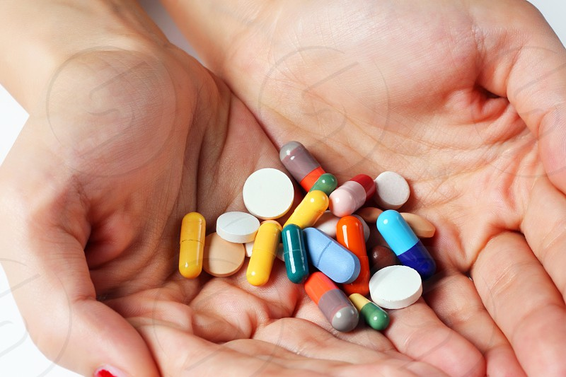 Pile of different pills in hands photo
