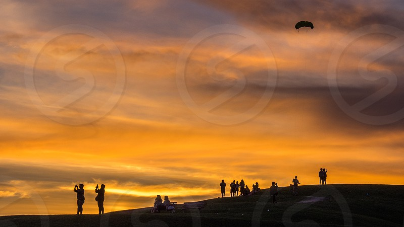 silhouette of people taking picture during sunset photo